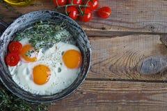 Uova fritte in vecchia padella con pane, i pomodori ciliegia, il pepe, il petrolio ed il timo, prima colazione sana Fotografia Stock Libera da Diritti