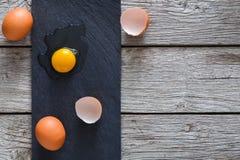Uova incrinate organiche di Brown con tuorlo su fondo di legno nero fotografie stock libere da diritti