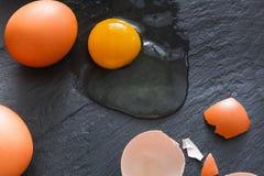 Uova incrinate organiche di Brown con tuorlo su fondo nero Immagini Stock Libere da Diritti