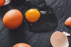 Uova incrinate organiche di Brown con tuorlo su fondo nero Fotografia Stock Libera da Diritti