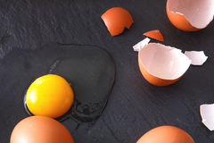 Uova incrinate organiche di Brown con tuorlo su fondo nero Immagine Stock Libera da Diritti