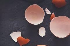 Uova incrinate organiche di Brown con tuorlo su fondo nero Fotografia Stock