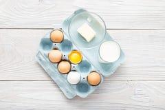Uova, latte e burro sopra la tavola di legno bianca Fotografia Stock