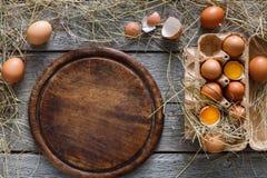 Uova marroni fresche in cartone su fondo di legno rustico Fotografia Stock