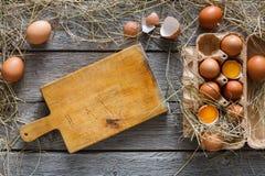 Uova marroni fresche in cartone su fondo di legno rustico Immagini Stock