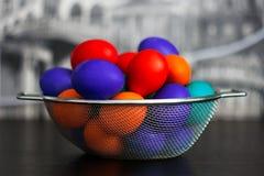 Uova multicolori per Pasqua in un canestro d'acciaio che sta sulla tavola Fotografia Stock