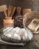 Uova negli utensili da cucina della cucina e del canestro Immagine Stock