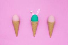 Uova nei coni della cialda su un fondo rosa Fotografia Stock