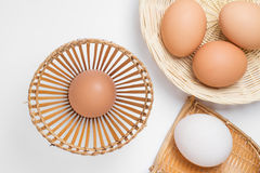 Uova nel canestro di tessuto di bambù su bianco Immagine Stock