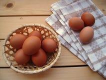 Uova nel canestro e sull'asciugamano di cucina su una tavola di legno, styl rustico fotografia stock