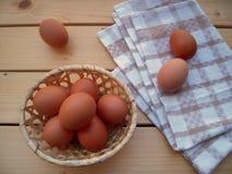Uova nel canestro e sull'asciugamano di cucina su una tavola rustica fotografia stock libera da diritti