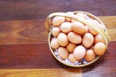 Uova nel canestro sul pavimento di legno Immagini Stock
