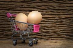 Uova nel carrello su vecchio bello fondo di legno, uova marroni nel canestro Immagine Stock