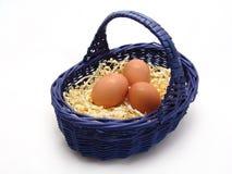 Uova nel cestino sui precedenti bianchi Immagine Stock
