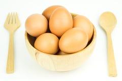 Uova nel cucchiaio e nella forchetta di legno della ciotola su fondo bianco Immagini Stock