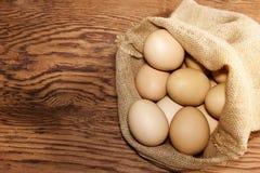 Uova nella borsa della tela di sacco sulla tavola di legno Fotografia Stock Libera da Diritti
