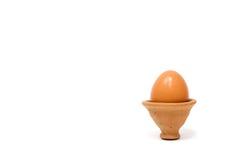 Uova nelle terraglie dell'argilla su fondo bianco Fotografia Stock