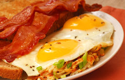 Uova, pancetta affumicata, pane tostato e patate tritate Immagini Stock