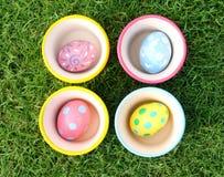 Uova pastelli con 4 tazze nel fondo dell'erba Fotografie Stock