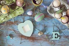 Uova, quaglia, decorazione di pasqua su una tavola di legno blu fotografie stock