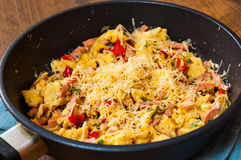 Uova rimescolate con il prosciutto, le verdure ed il formaggio in una padella Fotografia Stock Libera da Diritti