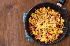 Uova rimescolate con il prosciutto, le verdure ed il formaggio in una padella Fotografia Stock