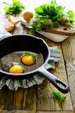 Uova rimescolate con le ortiche nella pentola sulla tavola di legno Fotografia Stock