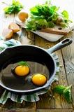 Uova rimescolate con le ortiche nella pentola sulla tavola di legno Fotografia Stock Libera da Diritti