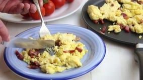 Uova rimescolate e pezzi del bacon alimentari con la forcella ed il coltello da un piatto stock footage