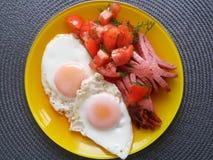Uova rimescolate, salsiccie fritte e pomodori affettati su un piatto giallo immagine stock libera da diritti