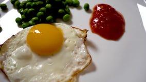 Uova rimescolate su un piatto bianco con i piselli e la salsa archivi video