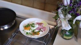 Uova rimescolate sul piatto su un piatto con la salsiccia La ragazza l video d archivio
