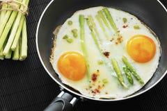Uova rimescolate in una padella con asparago Fotografie Stock