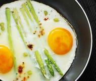Uova rimescolate in una padella con asparago Immagini Stock