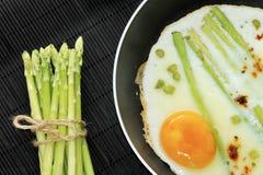 Uova rimescolate in una padella con asparago Immagini Stock Libere da Diritti
