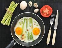 Uova rimescolate in una padella con asparago Fotografia Stock