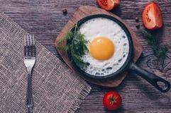 Uova rimescolate in una padella sulla tavola di legno, vista superiore di una tonalità Immagine Stock