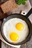 Uova rimescolate in una pentola del ferro sulla tavola di legno rustica Fotografie Stock