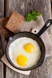 Uova rimescolate in una pentola del ferro sulla tavola di legno rustica Fotografie Stock Libere da Diritti