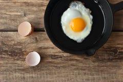 Uova rimescolate in una pentola del ferro sulla tavola rustica Immagine Stock