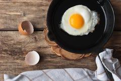 Uova rimescolate in una pentola del ferro sulla tavola rustica Immagini Stock Libere da Diritti