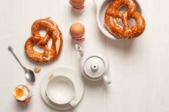 Uova sode e pasticcerie rustici della prima colazione su fondo di legno bianco immagini stock