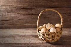 Uova in un canestro di vimini sulla tavola di legno Fotografie Stock Libere da Diritti