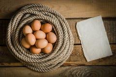 Uova in un canestro fatto dalla corda e dalla carta in bianco su una tavola di legno Immagini Stock Libere da Diritti