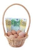 Uova in un cestino con soldi per Pasqua. Immagine Stock