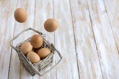 uova in un fondo di legno del canestro Immagini Stock