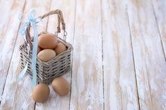 uova in un fondo di legno del canestro Fotografia Stock Libera da Diritti