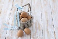 uova in un fondo di legno del canestro Immagini Stock Libere da Diritti