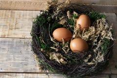 Uova in un nido su un supporto di legno stilizzato 2 Fotografia Stock