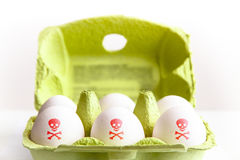 Uova in un pacchetto del Libro Verde con le uova dipinte con un cranio tossico rosso e le ossa di simbolo di rischio fotografia stock libera da diritti